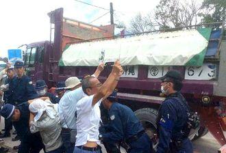 土砂を積んだダンプカーの進入に抗議する市民ら=10月25日午前10時半、東村高江・N1ゲート前