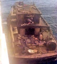 南雅和さんらベトナム難民105人が乗っていた木造船。翔南丸(左)に横付けし、難民らがよじ登ってきた=1983年8月4日、南シナ海(宮城元勝さん提供)