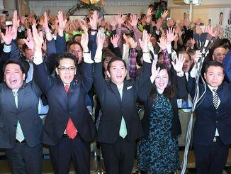 2期目の当選確実を決め支持者らとバンザイする松本哲治氏(中央)=12日午後9時35分、浦添市屋富祖の選対事務所