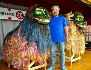 ふれあい交流獅子(左)の完成を喜ぶ眞島章次さん。神獅子(右)よりも一歩後ろに安置している=24日、仲西公民館