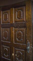 実家の木製ドアに残る傷やへこみ。サトルさんが殴るなどした跡だ=10月、本島内