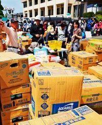 役場の敷地内に届いた水などの支援物資=4月16日午前11時10分ごろ、益城町役場(山城響撮影)