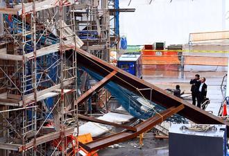 コンクリート製の梁(はり)が崩落した事故現場を調べる県警の捜査員=26日午後2時27分、那覇空港