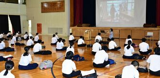 教師が役者に扮した寸劇を見て、新型コロナウイルス感染予防について学ぶ生徒ら=14日、宜野座中