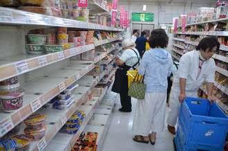 品不足となったインスタント食品などを補充するスーパーの従業員=2日午後、宮古島市平良下里のサンエーV21カママヒルズ食品館