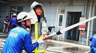 消防士の放水体験をする伊藝弥来君=4日、那覇市のなは市民協働プラザ
