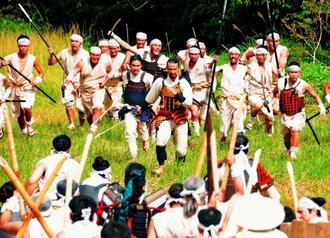 歴史ドラマ「尚巴志」の合戦シーンの撮影が始まった。島添大里城の軍と刀ややりなどで闘った=日、南城市の糸数城跡