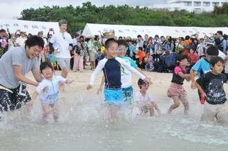 水しぶきを上げながら一斉に海に入る子どもたち=21日、石垣市真栄里・マエサトビーチ