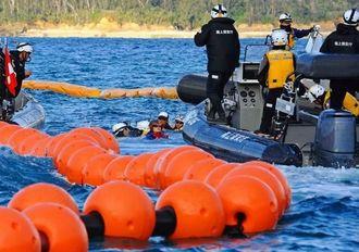 フロート設置に抗議して、制限水域内の海に飛び込んだ市民と制止する海上保安官=10日午後4時34分、名護市・大浦湾(国吉聡志撮影)