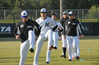 アップで体を動かすロッテの佐々木朗希選手(中央)=1日、石垣市中央運動公園野球場