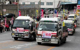 職員に見送られ、各地へ出発する初荷のトラック=3日午前9時30分ごろ、浦添市城間・オリオンビール本社