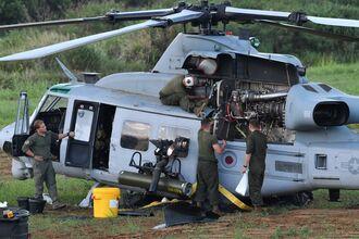 津堅島の畑に不時着した米軍の普天間飛行場所属のUH1ヘリのメンテナンス作業をする米兵=3日午後6時57分、うるま市津堅島(下地広也撮影)