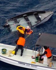 転覆したミニボートから男性と少年を救助する金城智彦さん(手前右)と玉城吉孝さん(同左)=8日午後1時すぎ(中城海上保安部提供)