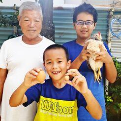 鶏を抱く渡名喜章介さん(右奥)と、弟の慶介さん(手前)、曾祖父の瑞慶覧朝光さん=12日、宜野湾市伊佐