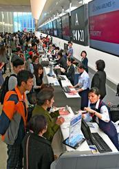 多くの利用客で混み合う際内連結ターミナルのカウンター=18日午前、那覇空港(国吉聡志撮影)
