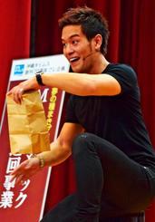 紙袋に入れたケチャップが消えるマジックを披露するMASAさん=19日、宜野座小学校