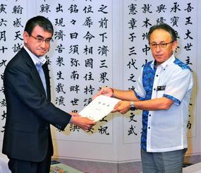 河野太郎外相(左)に基地負担軽減の要望書を手渡す玉城デニー知事=22日、県庁