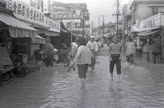 前線の通過に伴う豪雨で浸水した平和通り。女性もハイヒールを脱いで出勤=1962年3月20日