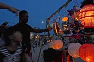 月が照らす中、住民手作りのちょうちんが並び淡い光が会場を包んだ=公民館前の水浜広場