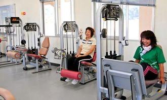 雑談しながらトレーニングを楽しむ利用者=国頭村浜の国頭陸上競技場トレーニングルーム