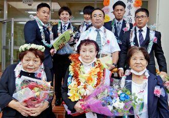 泊高校で一緒に学んだ級友たちに囲まれる米城惠子さん(前列左)と、宮里光子さん(同中央)=27日、那覇市の県立泊高校