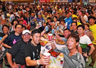 完走を目指し乾杯で気勢を上げる選手たち=17日夜、宮古島市総合体育館