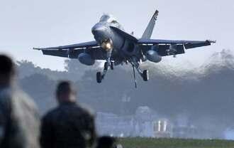 米軍普天間飛行場で着陸訓練する、岩国基地から飛来したFA18戦闘攻撃機。ワイヤーを引っ掛けるためのフック(機体後部)を出している=12日午後5時31分、宜野湾市(下地広也撮影)