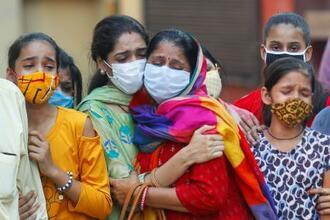 28日、インド・ニューデリーで新型コロナウイルスに感染した男性の死を悲しむ親族(ロイター=共同)