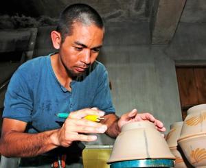 沖縄そば用の椀にクバ紋を彫り込む壺屋焼職人、賀数郁美さん=糸満市与座の「やちむん工房 結」