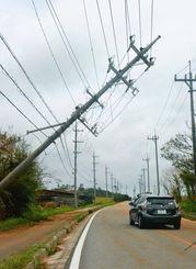 強風によって傾いた電柱=午前11時50分、石垣市星野地区(比嘉太一撮影)