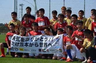 県内のサッカーチームと対戦し記念撮影する熊本の子どもたち=3日、金武町(伊藤和行撮影)