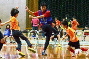 子どもたちとフットサルを楽しんだJ2讃岐の我那覇和樹(中央)=那覇市民体育館