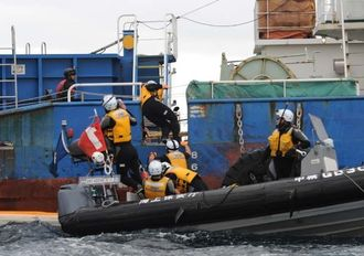 大型作業台船に乗り込んだ市民(左上)を追いかける海上保安官=9日午前10時45分ごろ、名護市辺野古沖