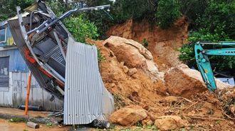 崩れた岩に押しつぶされた鉄工所=12日午前10時ごろ、本部町谷茶(国吉聡志撮影)