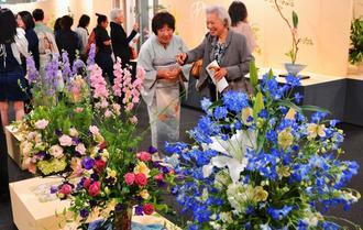 華美な生け花やフラワーアレンジメントを前に笑顔になる来場者ら=5日、那覇市久茂地・タイムスギャラリー