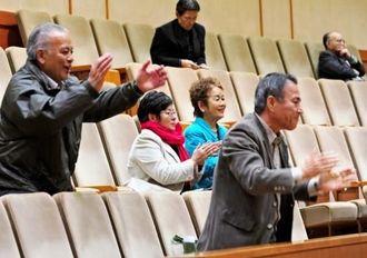 知事の辞任を求める抗議決議が可決され、立ち上がって拍手を送る傍聴者=10日午後10時14分、県議会