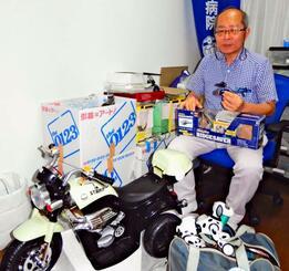 たくさんの部品をストックし、電動バイクやラジコンなどを修理する宮里勉さん=8月21日、那覇市おもろまちの自宅