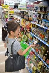 泡盛コーヒーを手に取る女性客=那覇市内の沖縄ファミリーマート