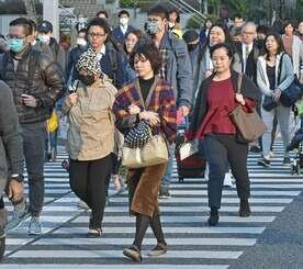 ストールや頭巾を身に着け、寒そうに交差点を渡る人たち=30日午前、那覇市久茂地