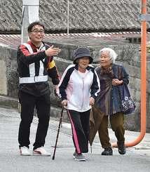 避難所に向かう高齢者を案内する関係者=9日午前、那覇市宇栄原