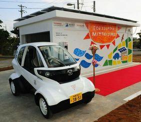 宮古島市内で運用が始まった小型電動自動車(手前)と太陽光発電を用いた充電ステーション=宮古島市役所下地庁舎