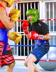 比嘉選手のしまくとぅばを「かっこいい」と感じる池本夢実さん(右)=2日、宜野湾市愛知、琉球ボクシングジム