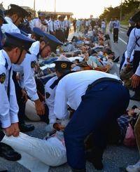 キャンプ・シュワブのゲート前の車道に寝転がり抗議する市民ら=21日午後4時40分、名護市辺野古