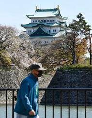 新型コロナウイルスの影響で閉園となった名古屋城近くをマスク姿で歩く人=10日午前、名古屋市