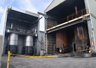 工場内の4基のうち左側の建物に、今回内部が爆発した焼却炉(左から2番目)、5月に爆発した焼却炉(左)がある。周辺にはタイヤが散乱していた=13日、糸満市西崎