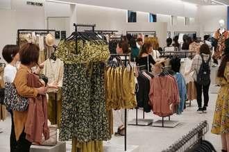 沖縄初出店の「ZARA」で洋服を手に取り買い物を楽しむ女性客ら=9日午前10時過ぎ、サンエー浦添西海岸パルコシティ
