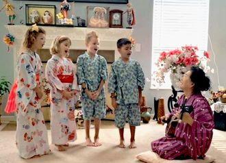 里子・コートランドさん(右)が奏でる三線に合わせ、「コロナ節」を歌う孫の四つ子たち=米国オハイオ州コロンバス市の里子さん宅