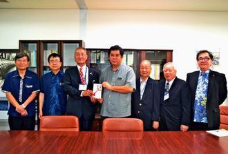 琉球華僑総会の張本光輝会長(左から3人目)が台湾人観光客への医療費寄付金の残金を県の砂川靖保健医療部長(同4人目)に贈呈した=9日、沖縄県庁