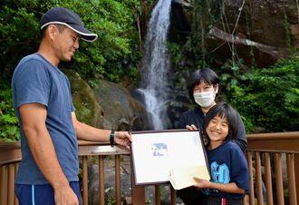 写真入りの記念証と入園券を手渡され満面の笑みを浮かべる辺土名美央さん(右手前)=12日、轟の滝公園・名護市数久田