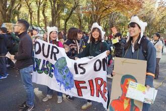 東京都に気候非常事態宣言を出すよう求め、都庁周辺を行進する若者ら=11月、東京都新宿区